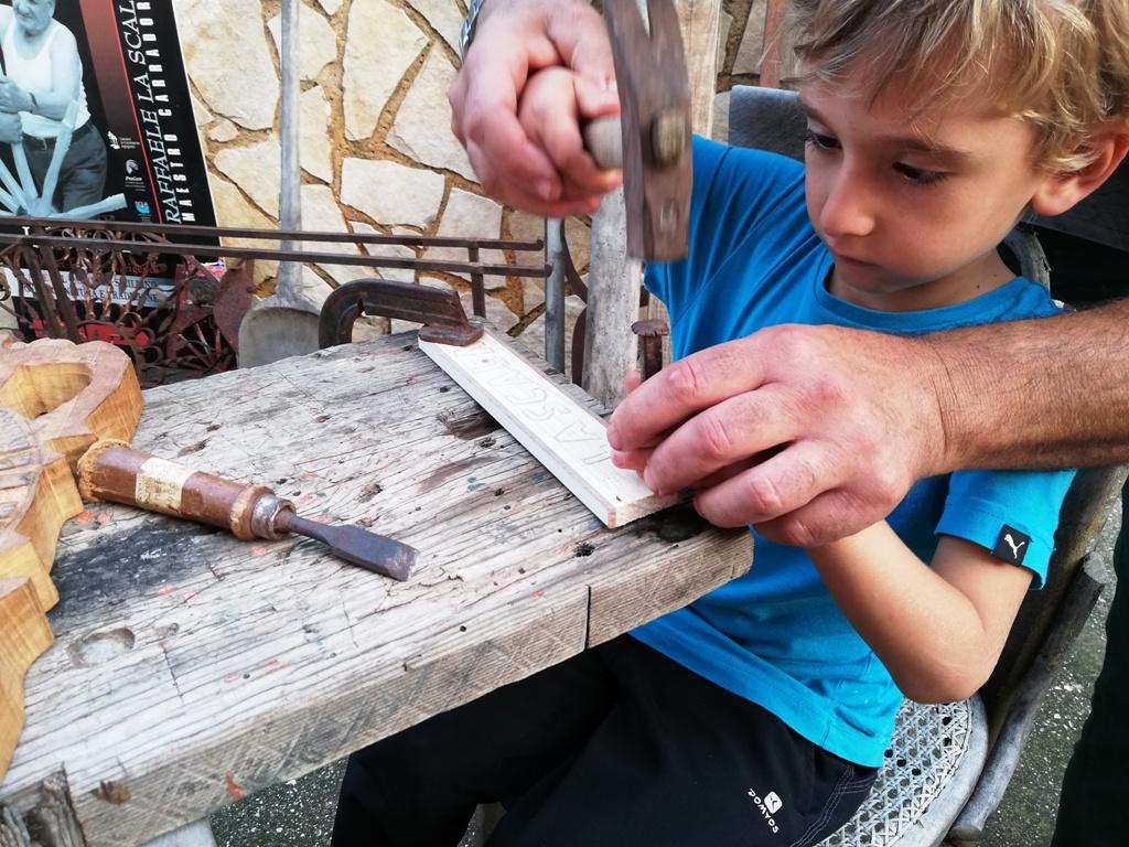 bambino che impara l'arte del carretto siciliano