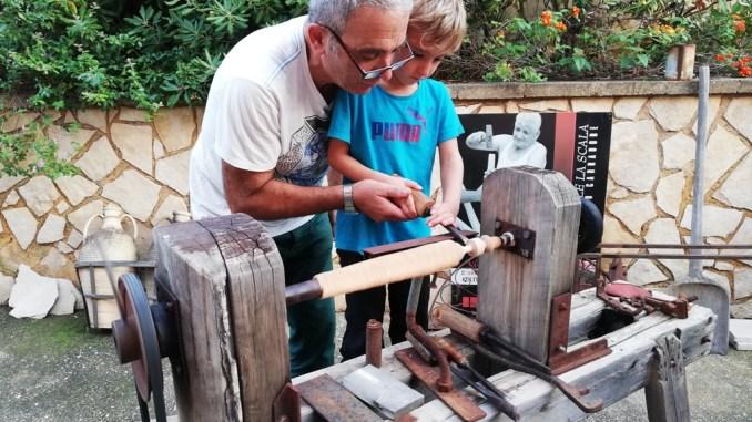 un bambino che impara l'arte del carretto siciliano
