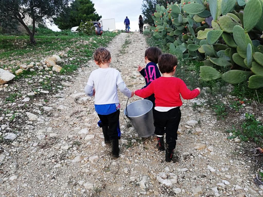 bimbi che trasportano un secchio con il latte