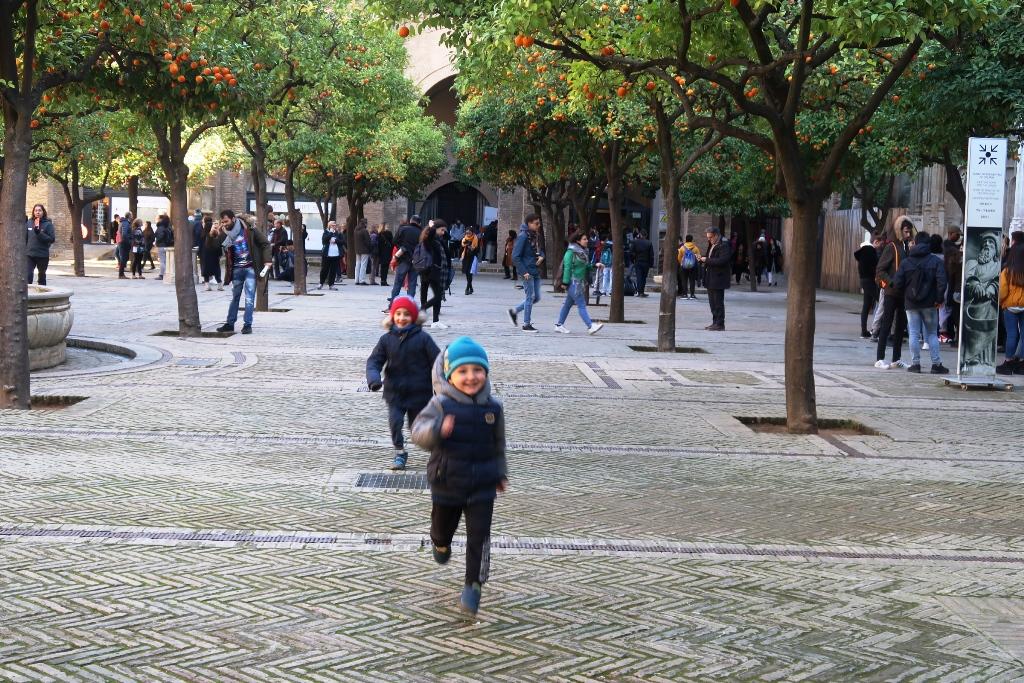 bambini che corrono al patio de los naranjos di siviglia