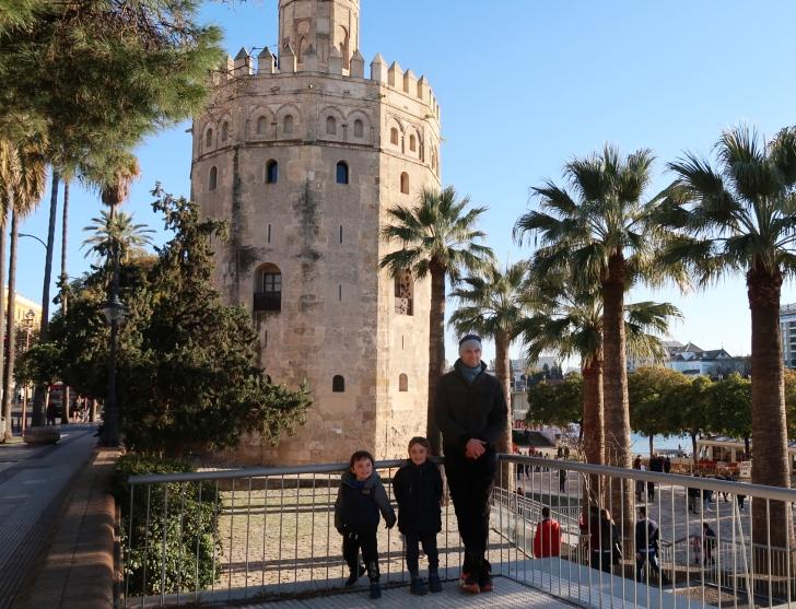 un papà con i suoi bambini davanti la Torre del oro di Siviglia