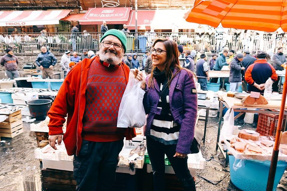 una donna che compra il pesce al mercato del pesce di Catania