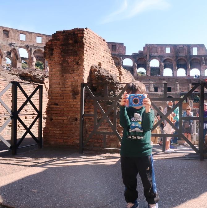 bambino che scatta una foto al Colosseo