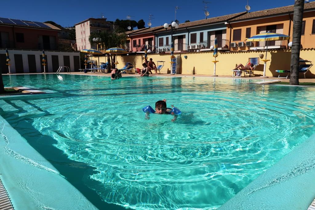 bimbo che nuota in piscina in una casa vacanze al mare ad Agrigento