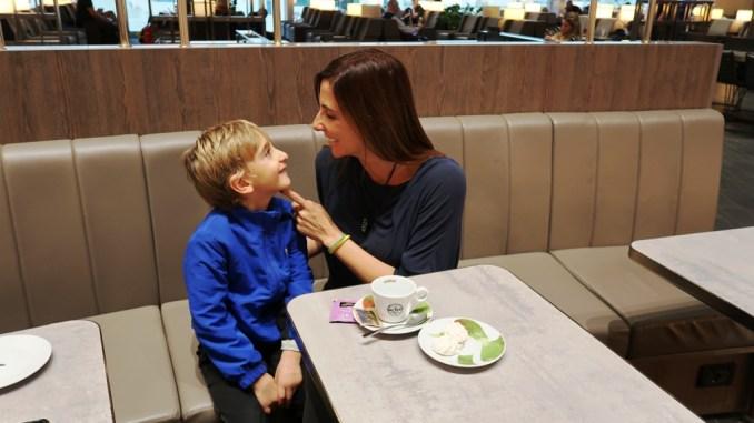 una mamma e un bambino seduti alla Plaza Premium Lounge di Fiumicino