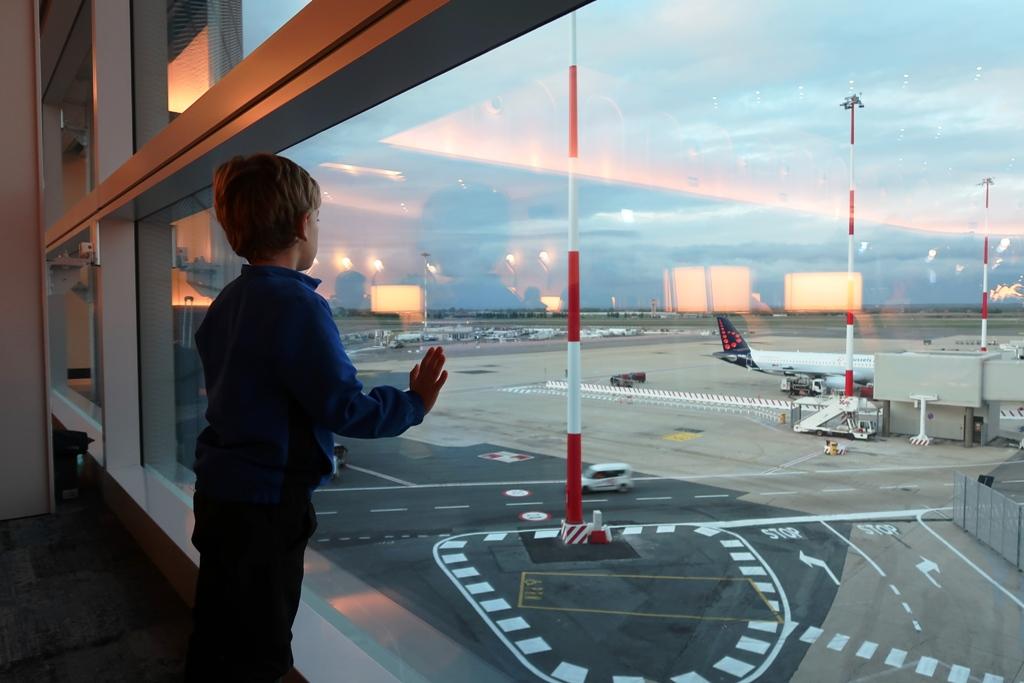 un bambino che guarda gli aerei dalla Plaza Premium Lounge di Fiumicino