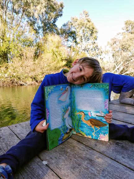 un bambino che legge un libro sulla leggenda della ninfa Ciane e Anapo