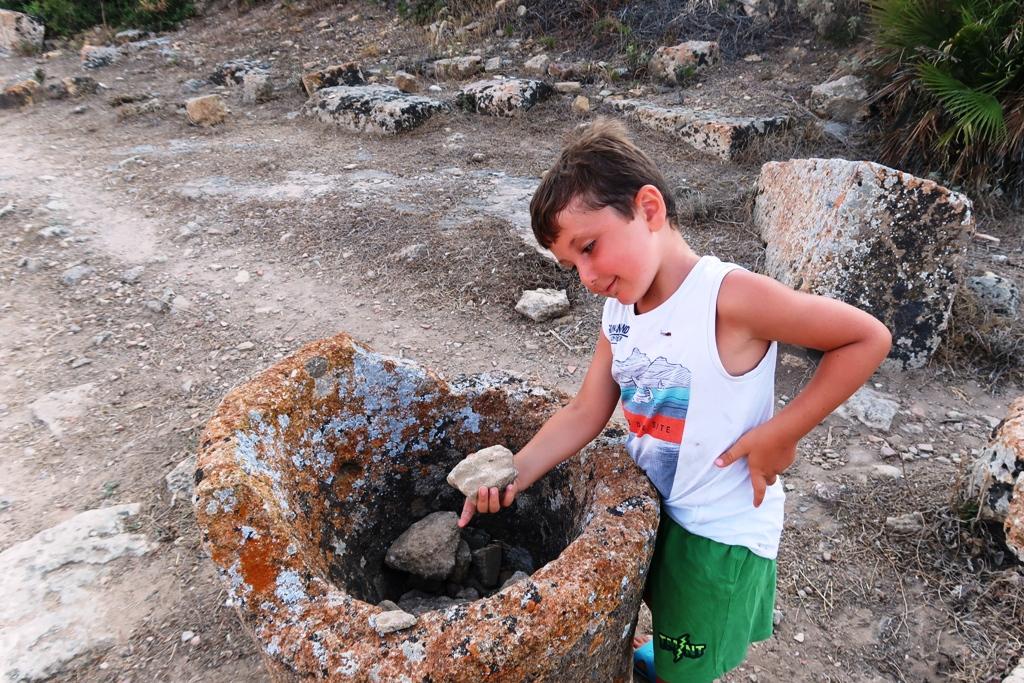bambino che tiene un reperto archeologico a selinunte