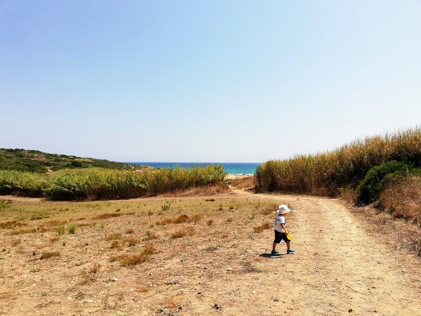 bimbo che cammina sulla spiaggia della pizzuta vicino Noto