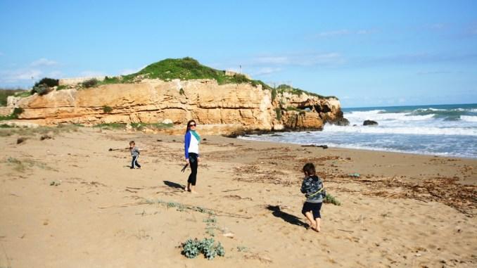 una mamma e due bambini sulla spiaggia di Eloro
