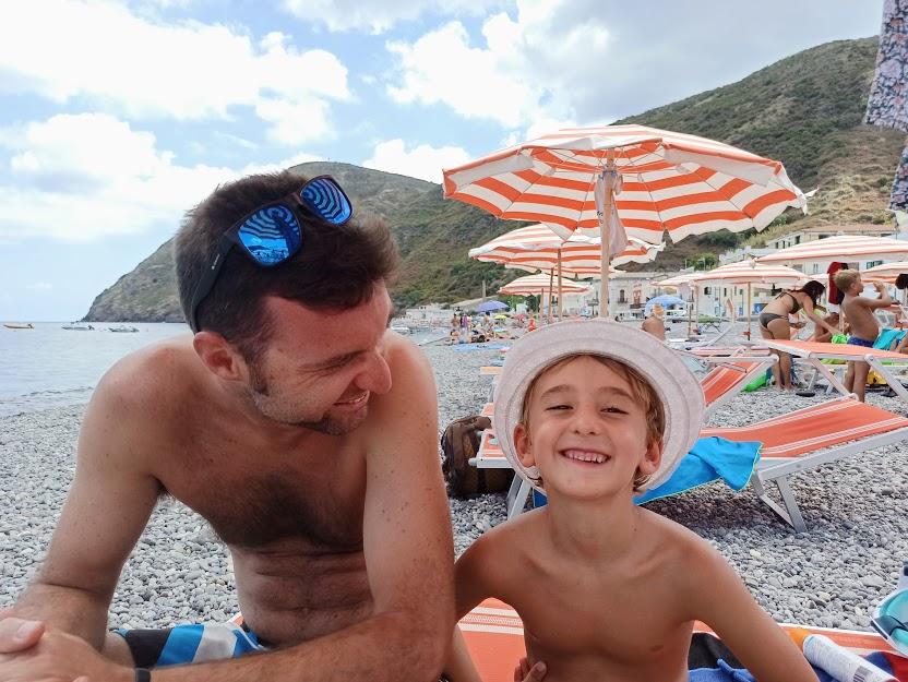 un papà e un bambino che sorridono nella spiaggia di Lipari