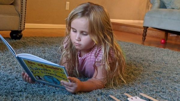 Charlotte reading book 2 with her characters