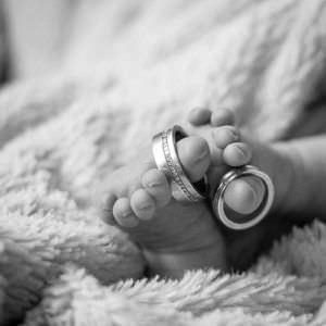 Wedding rings on a newborn babies toes