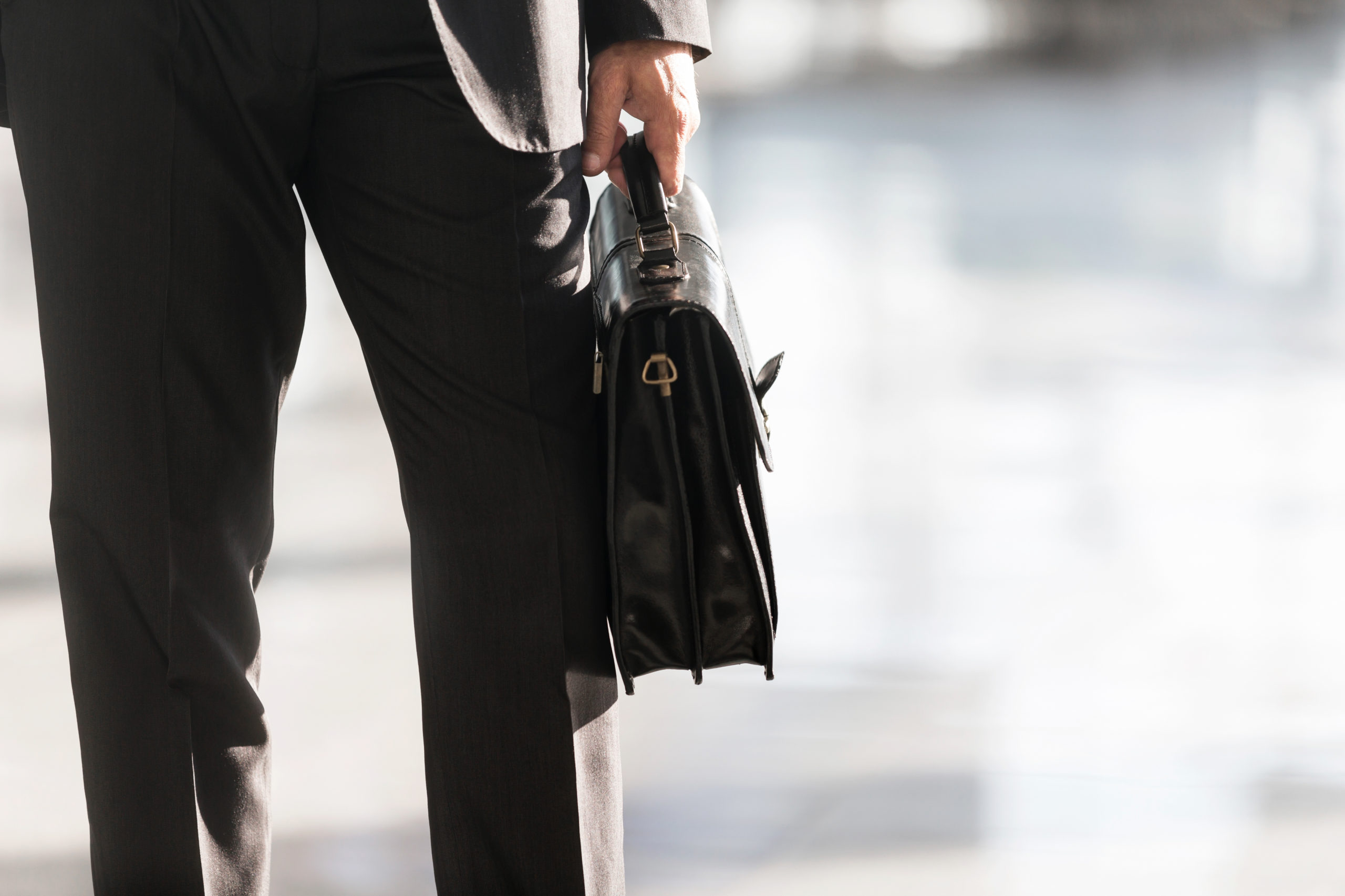 man in a suit holding a carry on bag