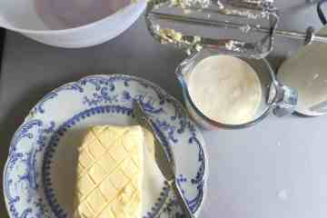 Freshly made and shaped butter on a blue plate with the buttermilk in a jug by the side.