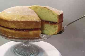 Victoria Sponge cake on a glass cake stand.
