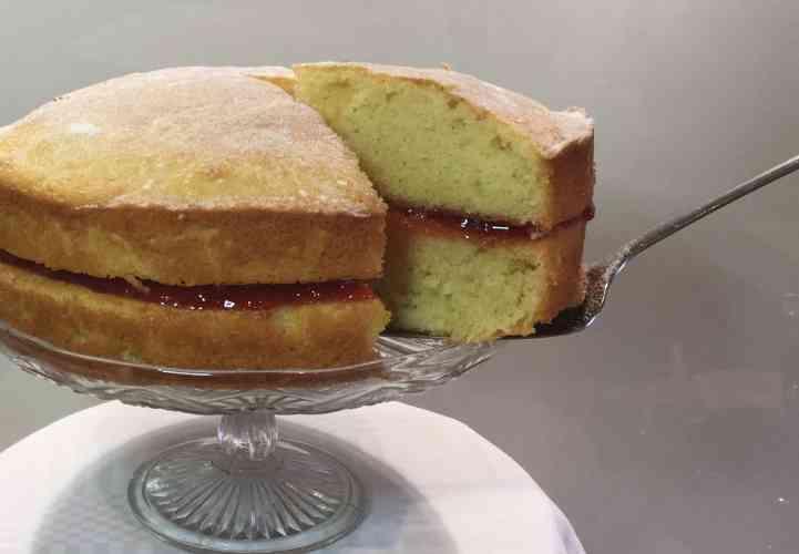 Victoria Sponge cake on a glass cake stand.