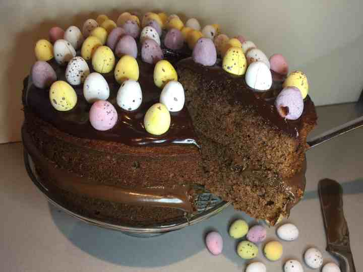 Chocolate Cake. Decorated with mini sugar coated eggs. Displayed on a glass cake stand.