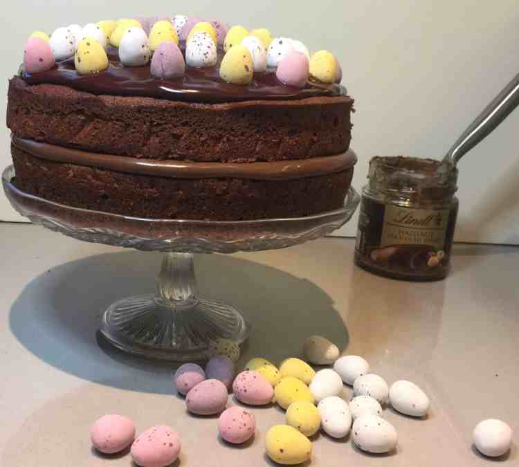 Chocolate Cake with Lindt Hazelnut chocolate spread filling. Decorated with mini sugar coated eggs. Displayed on a glass cake stand.