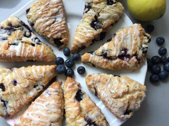 8 portions of Lemon glazed blueberry scones on a white plate.