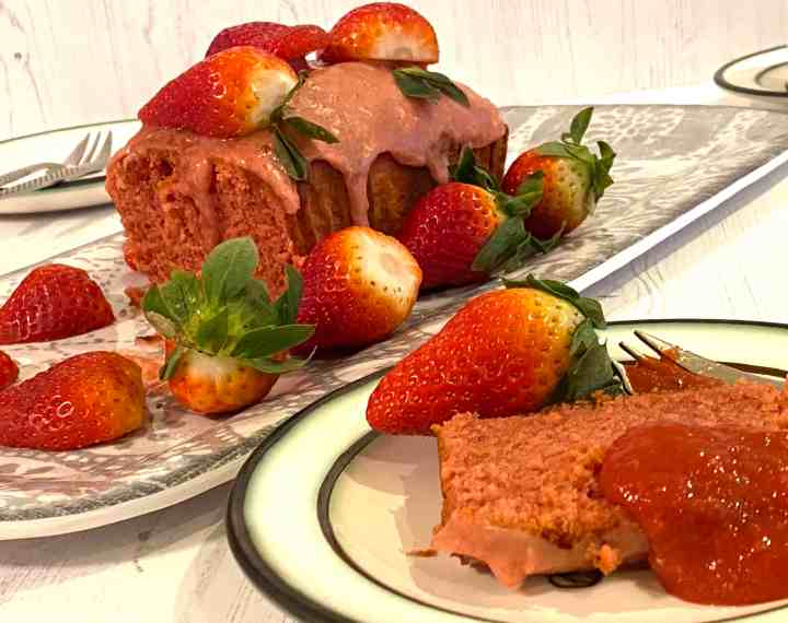 Strawberry cake on a grey dish with fresh strawberries