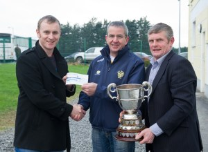 Chairman of Newmarket GAA Pat Keogh, centre, is presented with a cheque to the value of €3500  by Owen Ryan, of The Clare Champion watched by Joe Cooney, vice chairman Clare GAA, following their Clare Champion Cup final win at Clarecastle. Meanwhile, the Inagh-Kilnamona club recieved a cheque to the value of  €1500. Photograph by John Kelly.