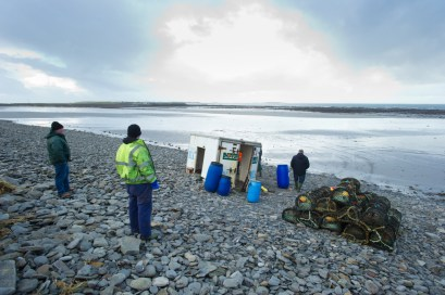 Fishermen salvaged what equipment they could from a container after it was washed off the pier at Seafield, Quilty and sent a half a mile across the beach. Photograph by John Kelly.