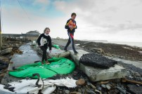 Paul and Lisa Keating negotiate the rubble strewn road while making their way home from the shop with supplies in Kilbaha village where the main road is covered by rocks, undermined in places and cut off following the latest high seas and gales at Kilbaha. Photograph by John Kelly.
