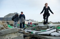 Locals negotiates their way through the trail of destruction on the main road in Kilbaha village which is cut off to traffic following the latest high seas and gales. Photograph by John Kelly.