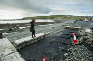A woman negotiates her way through the trail of destruction on the main road in Kilbaha village which is cut off to traffic following the latest high seas and gales. Photograph by John Kelly.
