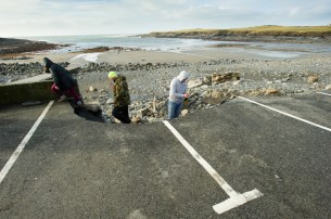 People examine part of a badly damaged car parking area at White Strand, Miltown Malbay following the latest high seas and gales. Photograph by John Kelly.