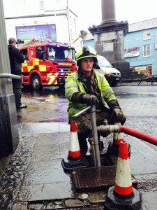 An Ennis fireman setting up to flush the drains in O'Connell Street, Ennis. Photograph by John Kelly