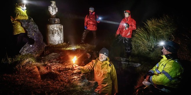 New Year's Eve at St Enda's Well, Slieve Elva, Fanore. Tom Doherty of Doolin Coastguard lights a torch to leave inside the well chamber, in memory of all who have lost their lives at sea over the past year, Looking on are, Celina Kennedy, David Courtney, former Coastguard helicopter pilot, John Galvin, MD Clare Champion and Joe Queally of the RNLI. Photograph by John Kelly.