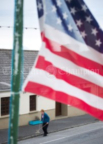 The US flag flying high in the Long Village, as a local brushes up the footpath outside her premised, ahead of the visit of the United States President Donald J. Trump to Doonbeg. Photograph by John Kelly