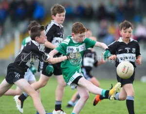 Jack Flavin of Kilrush in action against Ian Ryan of Doonbeg during their Primary Schools Div 2 Football 13-Aside final at Kilrush. Photograph by John Kelly