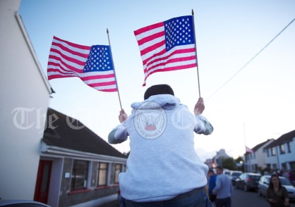 A boy waves with his flags ahead of a walkabout by Eric and Don Junior Trump in Doonbeg Village. Photograph by John Kelly