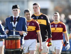 Gordon Kelly (C) of Miltown, leads the team behind the pipe band before their senior football county final replay at Cusack Park. Photograph by John Kelly.