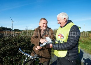 Joe Queally offers black pudding and brown bread to Pat Whelan on his trusty bike while taking part in the Shades Of Autumn 10k walk in aid of the RNLI on bank Holiday Monday at Shragh. Photograph by John Kelly.