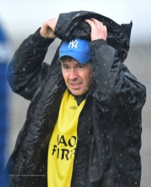 Clare mentor Ken Ralph does battle with the elements on the sideline during their National League game against Laois at Cusack Park. Photograph by John Kelly