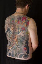 Tiger full back tattoo with leaves, seaweed and waves