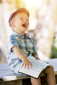 Child laughing with book