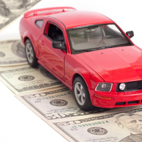 red car on a street of money