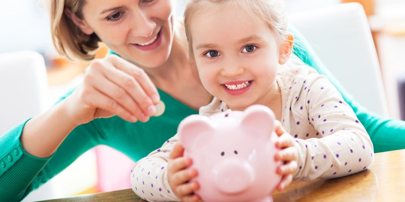 Mom and daughter with piggy bank