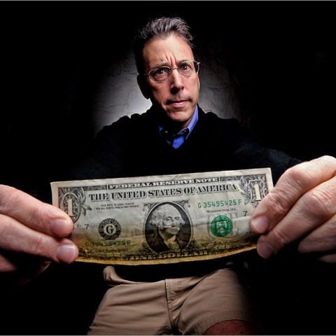 Clark Howard holds a dollar bill
