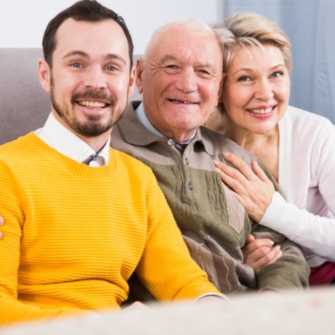 Smiling grandfather, grandson and his mother hugging sitting on sofa at home