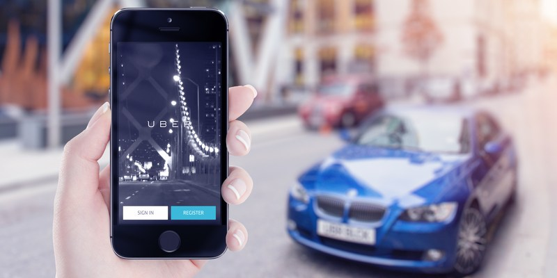 Apple iPhone with Uber app and car