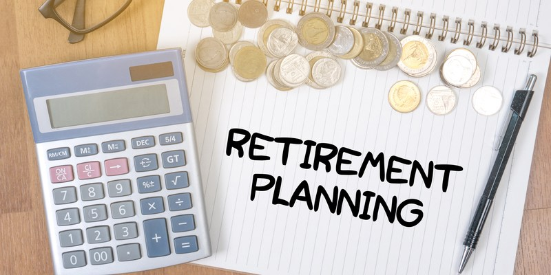 'retirement planning' written on a notebook with a calculator and coins