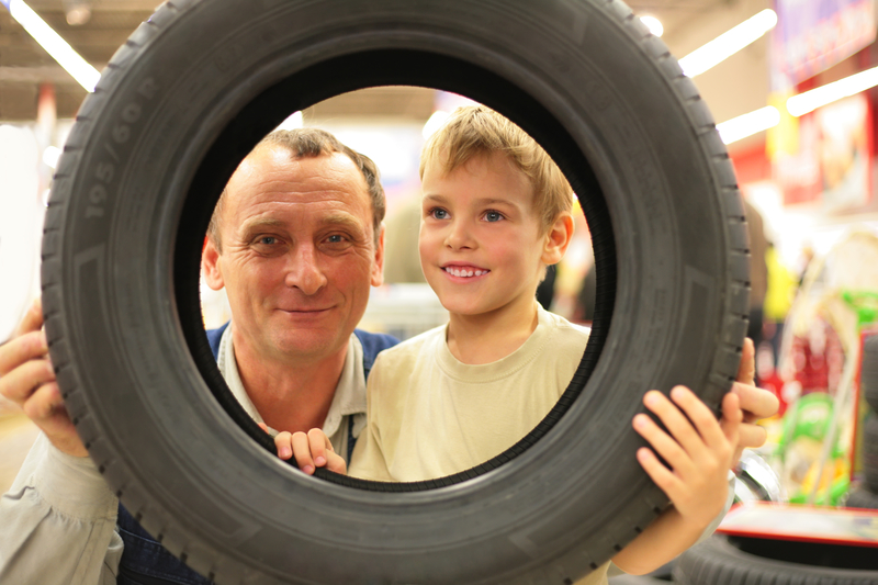 parent and child shopping for tires in a store
