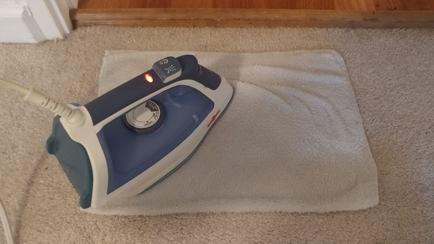 Step 3: Set iron to medium heat and apply it to the towel, moving