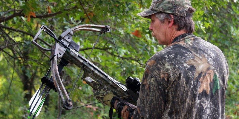 Hunter in camouflage holding a crossbow